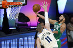 Boston Celtics' Jayson Tatum, right, heads to the basket as Milwaukee Bucks' Brook Lopez (11) defends during the first half of an NBA basketball game Friday, July 31, 2020, in Lake Buena Vista, Fla. (AP Photo/Ashley Landis, Pool)