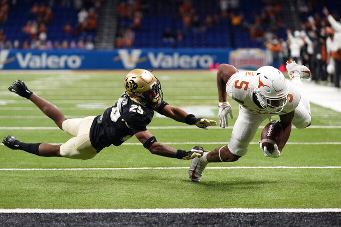 Texas running back Bijan Robinson (5) runs for a touchdown past Colorado cornerback Mekhi Blackmon (25) during the first half of the Alamo Bowl NCAA college football game, Tuesday, Dec. 29, 2020, in San Antonio. (AP Photo/Eric Gay)