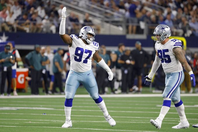 Dallas Cowboys defensive tackle Osa Odighizuwa (97) and defensive end Brent Urban (95) celebrate after Odighizuwa sacked Philadelphia Eagles quarterback Jalen Hurts in the first half of an NFL football game in Arlington, Texas, Monday, Sept. 27, 2021. (AP Photo/Ron Jenkins)