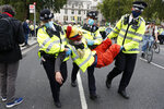 Police detain demonstrators who where sitting on the road blocking traffic during an Extinction Rebellion climate change protest in London, Tuesday, Sept 1, 2020. (AP Photo/Alastair Grant)