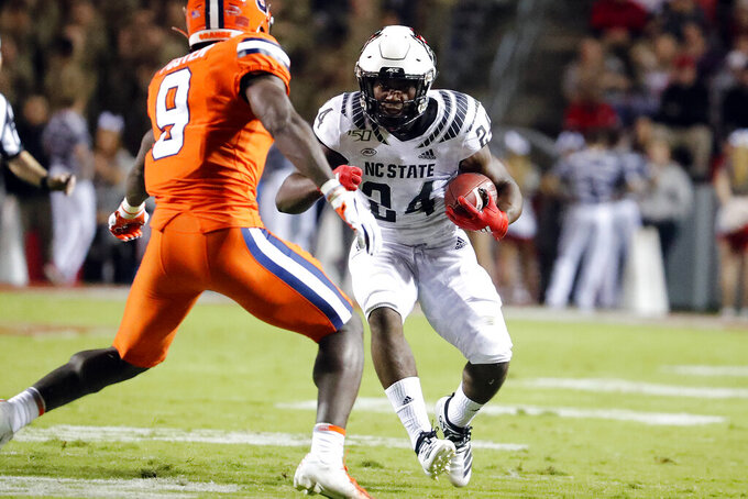 North Carolina State's Zonovan Knight (24) looks to get past Syracuse's Evan Foster (9) during the first half of an NCAA college football game in Raleigh, N.C., Thursday, Oct. 10, 2019. (AP Photo/Karl B DeBlaker)