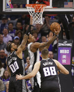 San Antonio Spurs guard DeMar DeRozan, center, goes to the basket against Sacramento Kings' Willie Cauley-Stein, left, and Nemanja Bjelica, right, during the first quarter of an NBA basketball game Monday, Feb. 4, 2019, in Sacramento, Calif.(AP Photo/Rich Pedroncelli)