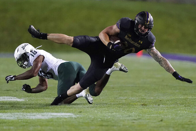 Northwestern tight end Trey Pugh, right, is tackled by Michigan State cornerback Kalon Gervin during the second half of an NCAA college football game in Evanston, Ill., Friday, Sept. 3, 2021. Michigan State won 38-21. (AP Photo/Nam Y. Huh)