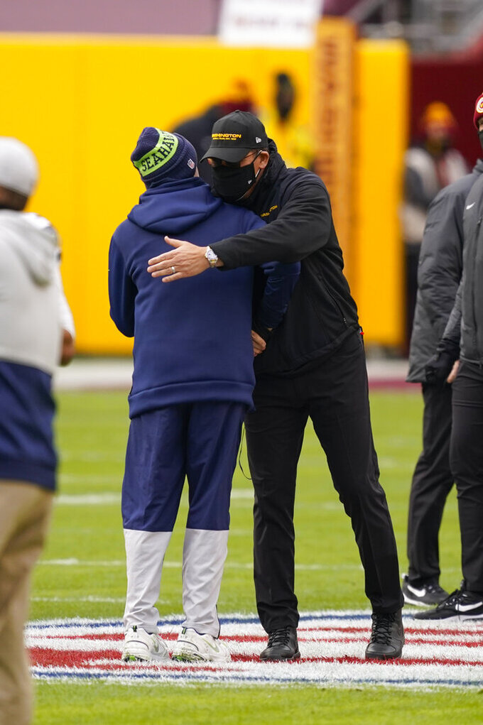 Seattle Seahawks head coach Pete Carroll, left, and Washington Football Team head coach Ron Rivera, right, greeting each other before the start of an NFL football game, Sunday, Dec. 20, 2020, in Landover, Md. (AP Photo/Andrew Harnik)
