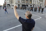 A protester holds up his fist as police officers watch during a protest over the deaths of George Floyd and Breonna Taylor, Saturday, May 30, 2020, in Louisville, Ky. Breonna Taylor, a black woman, was fatally shot by police in her home in March. (AP Photo/Darron Cummings)