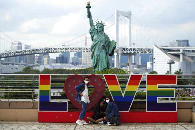 Visitors, wearing face masks, gather in front of the Statue of Liberty replica Thursday, April 8, 2021, in Tokyo. Tokyo has asked Japan's central government for permission to implement emergency measures to curb a surge in a rapidly spreading and more contagious coronavirus variant, just over three months before the start of the Olympics. (AP Photo/Eugene Hoshiko)