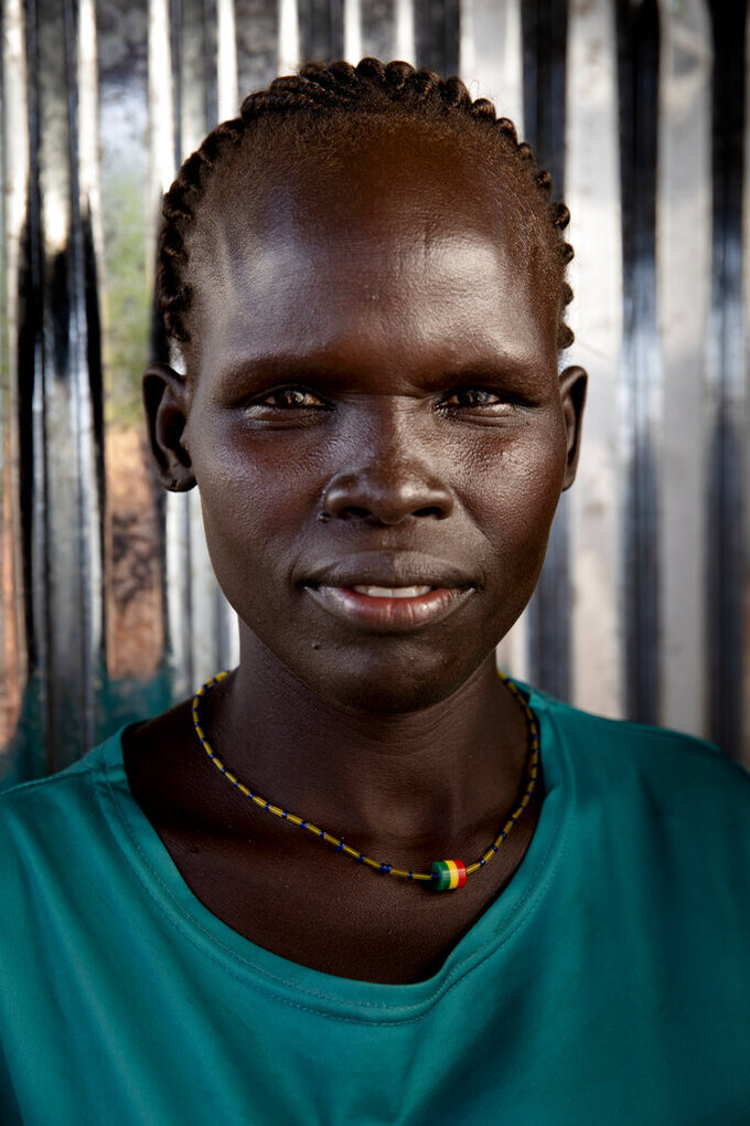 Oum Djima, 32-years-old mother of 5, poses for a portrait at Paska Itwari Beda's Juba, South Sudan home, Saturday, May 29, 2021. With resources scarce, Beda and nine women formed a group that meets and contributes two of the barest necessities for warding off hunger and illness _ money and bars of soap.They gather on Fridays, pooling supplies and handing them out to a different family every week. Over coffee, they share advice. (AP Photo/Adrienne Surprenant)