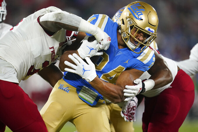 UCLA running back Zach Charbonnet is tackled by Fresno State defensive end Arron Mosby, left, and another defender during the first half of an NCAA college football game Saturday, Sept. 18, 2021, in Pasadena, Calif. (AP Photo/Marcio Jose Sanchez)