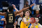 Michigan guard Franz Wagner (21) drives to the basket ahead of Florida State forward Malik Osborne (10) during the first half of a Sweet 16 game in the NCAA men's college basketball tournament at Bankers Life Fieldhouse, Sunday, March 28, 2021, in Indianapolis. (AP Photo/Jeff Roberson)