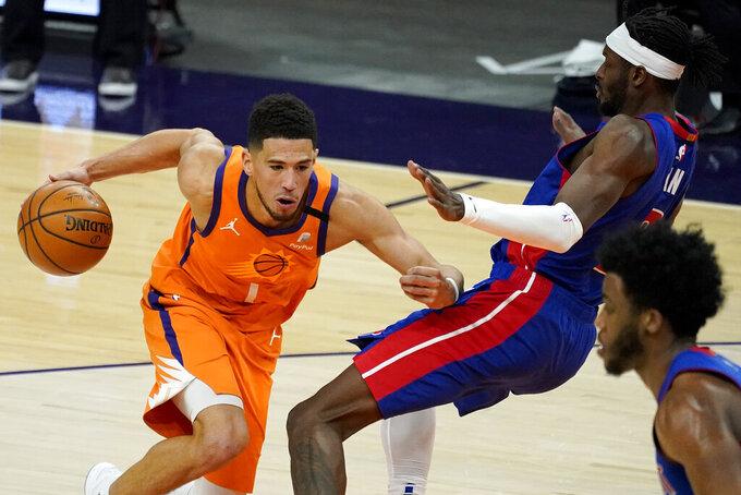 Phoenix Suns guard Devin Booker (1) fouls Detroit Pistons forward Jerami Grant during the second half of an NBA basketball game, Friday, Feb. 5, 2021, in Phoenix. (AP Photo/Matt York)