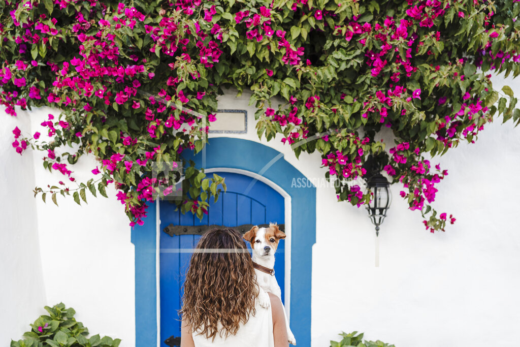 Woman with dog in front of flowering plant on wall