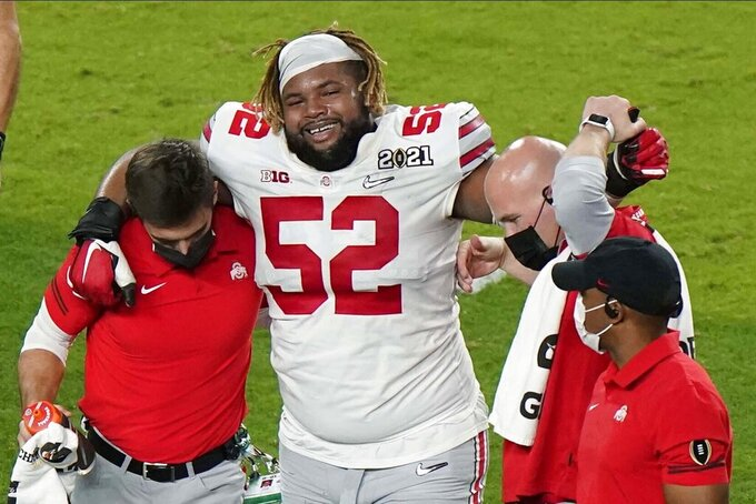 Ohio State offensive lineman Wyatt Davis is helped off the field after he was hurt during the first half of an NCAA College Football Playoff national championship game against Alabama, Monday, Jan. 11, 2021, in Miami Gardens, Fla. (AP Photo/Wilfredo Lee)