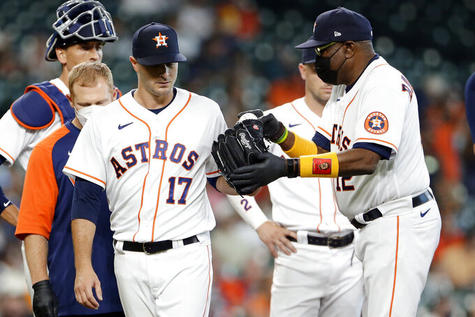 Houston Astros starting pitcher Jake Odorizzi (17) hands the ball off to manager Dusty Baker Jr. (12) as he leaves the mound with an injury on the second batter of the first inning of a baseball game agains the Los Angeles Angels Saturday, April 24, 2021, in Houston. (AP Photo/Michael Wyke)