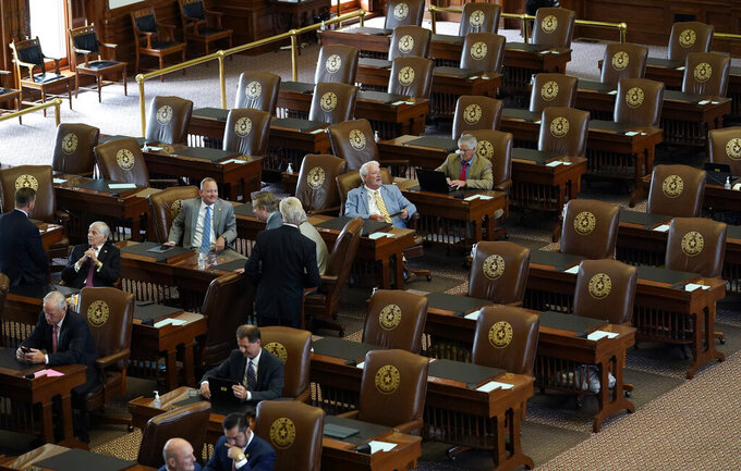 FILE - In this July 13, 2021, file photo empty seats are seen in the House Chamber at the Texas Capitol in Austin, Texas. Texas Democrats left the state to block sweeping new election laws, while Republican Gov. Greg Abbott threatened them with arrest the moment they return. (AP Photo/Eric Gay, File)