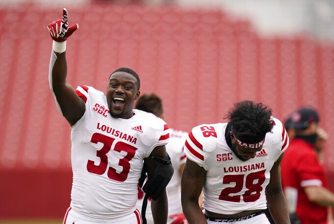 Louisiana-Lafayette linebacker Tyler Guidry (33) and teammate Ja'len Johnson (28) celebrate as they run off the field after an NCAA college football game against Iowa State, Saturday, Sept. 12, 2020, in Ames, Iowa. Louisiana-Lafayette won 31-14. (AP Photo/Charlie Neibergall)