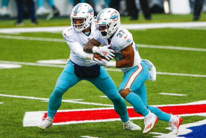 Miami Dolphins quarterback Tua Tagovailoa (1) fakes a hand off to running back Myles Gaskin (37) in the first half of an NFL football game against the Buffalo Bills, Sunday, Jan. 3, 2021, in Orchard Park, N.Y. (AP Photo/John Munson)