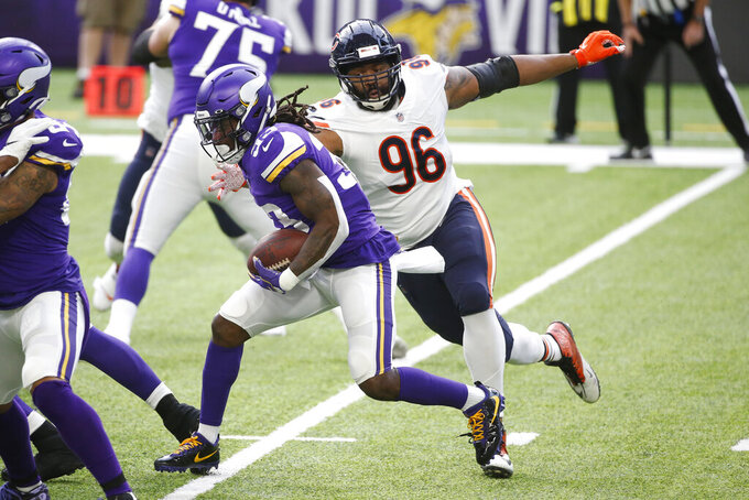 Minnesota Vikings running back Dalvin Cook, left, runs from Chicago Bears defensive tackle Akiem Hicks (96) during the first half of an NFL football game, Sunday, Dec. 20, 2020, in Minneapolis. (AP Photo/Bruce Kluckhohn)