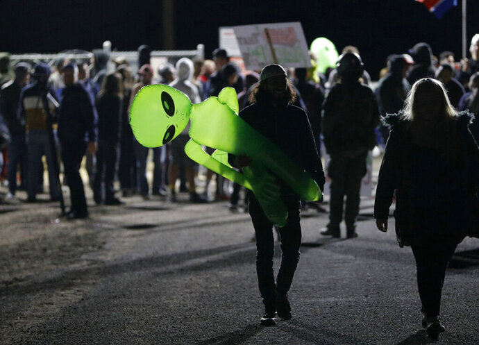 A mans holds an inflatable alien at an entrance to the Nevada Test and Training Range near Area 51 Friday, Sept. 20, 2019, near Rachel, Nev. People gathered at the gate inspired by the