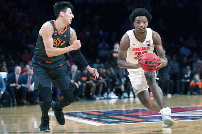 Syracuse forward Elijah Hughes (33) drives against Oklahoma State guard Lindy Waters III during the second half of an NCAA college semi final basketball game in the NIT Season Tip-Off tournament, Wednesday, Nov. 27, 2019, in New York. Oklahoma State won 86-72. (AP Photo/Mary Altaffer)