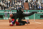 FILE - In this June 7, 2009, file photo, an unidentified person is grabbed by security during the men's singles final match between Switzerland's Roger Federer and Sweden's Robin Soderling at the French Open tennis tournament in Paris. (AP Photo/Lionel Cironneau, File)