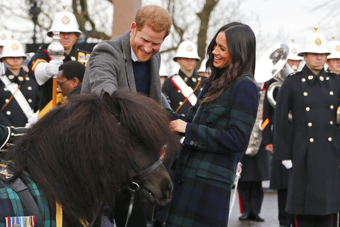Britain's Prince Harry and his fiancee Meghan Markle meet a Shetland Pony as they arrive at Edinburgh Castle in Edinburgh, Scotland, Tuesday, Feb. 13, 2018. The recently engaged couple are on a one day tour to Edinburgh, and will visit the Castle and observe the firing of the One O'clock Gun. (AP Photo/Frank Augstein)