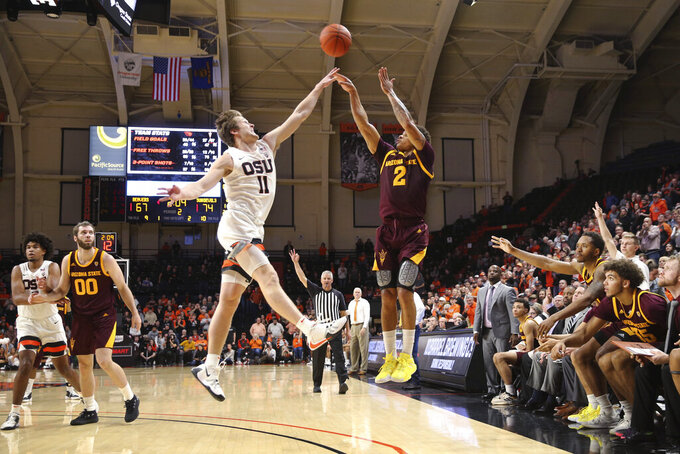 Arizona State's Rob Edwards, center right, shoots a 3-pointer over Oregon State's Zach Reichle during the second half of an NCAA college basketball game in Corvallis, Ore., Thursday, Jan. 9, 2020. (AP Photo/Chris Pietsch)