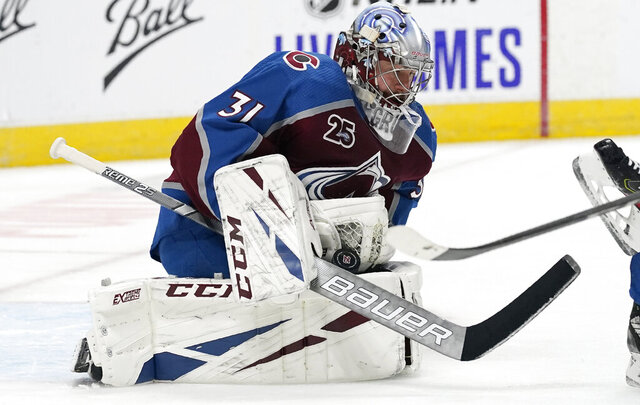Colorado Avalanche goaltender Philipp Grubauer stops the puck on a shot by the San Jose Sharks during the second period of an NHL hockey game Tuesday, Jan. 26, 2021, in Denver. (AP Photo/David Zalubowski)