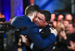 NCAA college football player, LSU quarterback Joe Burrow, left, hugs his coach Ed Orgeron after he is announced as the Heisman Trophy winner, Saturday, Dec. 14, 2019, in New York. (Todd Van Emst/Pool Photo via AP)