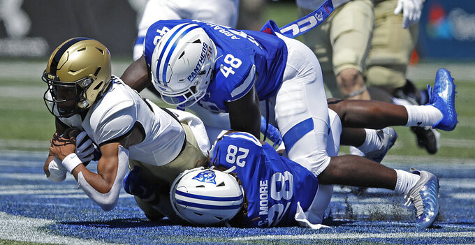 Army quarterback Christian Anderson, left, is tackled by Georgia State's Justin Abraham (48) and Chris Moore (28) during the first half of an NCAA football game Saturday, Sept. 4, 2021, in Atlanta. (AP Photo/Ben Margot)