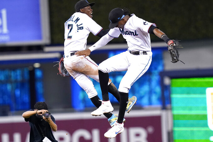 Miami Marlins' Jazz Chisholm Jr. (2) and Lewis Brinson, right, celebrate after a baseball game against the New York Mets, Thursday, Aug. 5, 2021, in Miami. The Marlins won 4-2. (AP Photo/Lynne Sladky)