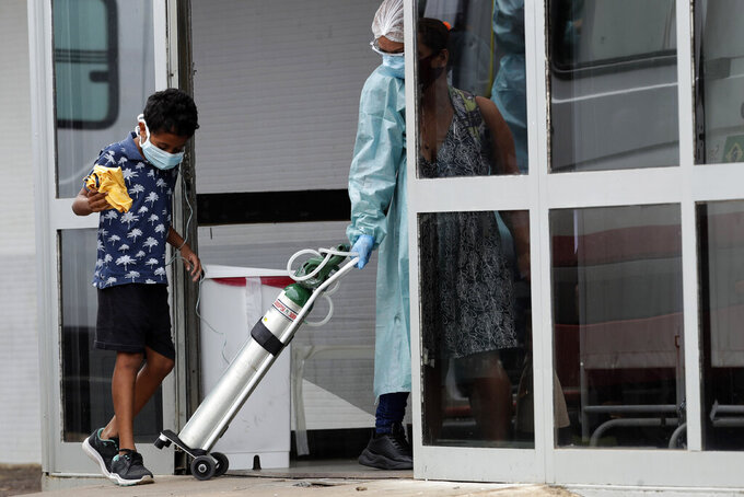 A healthcare worker rolls in an oxygen cylinder used by a boy suspected of having COVID-19 as he enters the public HRAN Hospital in Brasilia, Brazil, Thursday, March 11, 2021. The HRAN is the reference hospital for the treatment of the new coronavirus cases. (AP Photo/Eraldo Peres)