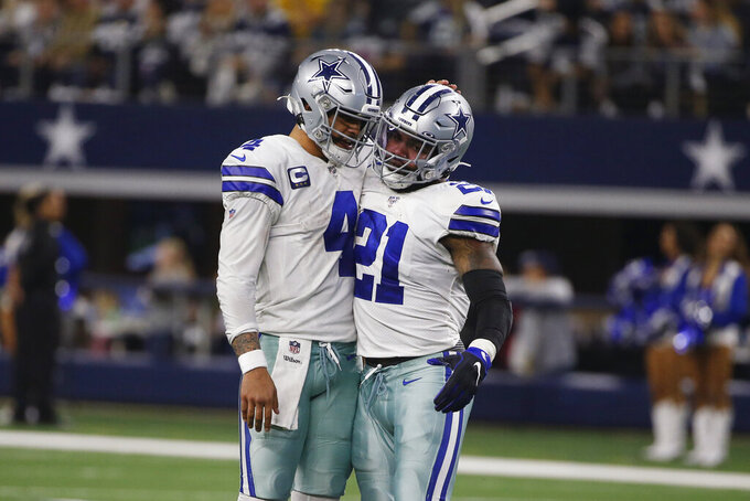 Dallas Cowboys quarterback Dak Prescott (4) and running back Ezekiel Elliott (21) embrace after a touchdown against the Washington Redskins during the second half of an NFL football game in Arlington, Texas, Sunday, Dec. 15, 2019. (AP Photo/Ron Jenkins)