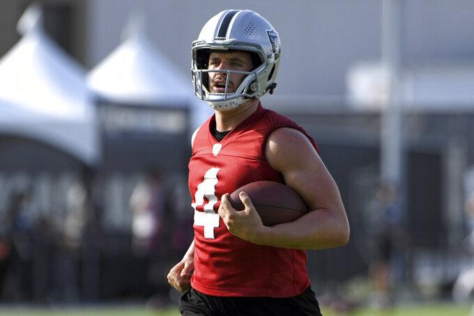 Las Vegas Raiders quarterback Derek Carr carries the ball during an NFL football practice Thursday, July 29, 2021, in Henderson, Nev. (AP Photo/David Becker)