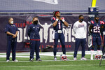 """New England Patriots including head coach Bill Belichick, left, quarterback Cam (1) and defensive back Terrence Brooks (25) stand during the singing of """"Lift Every Voice and Sing"""" before an NFL football game against the Miami Dolphins, Sunday, Sept. 13, 2020, in Foxborough, Mass. (AP Photo/Charles Krupa)"""