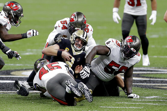 New Orleans Saints quarterback Drew Brees, center, is tackled between Tampa Bay Buccaneers' Devin White (45), Lavonte David (54) and Rakeem Nunez-Roches (56) during the first half of an NFL divisional round playoff football game, Sunday, Jan. 17, 2021, in New Orleans. (AP Photo/Brett Duke)