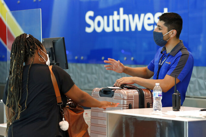 FILE - In this June 24, 2020 file photo, Southwest Airlines employee Oscar Gonzalez, right, assists a passenger at the ticket counter at Love Field in Dallas. Southwest Airlines says flights are getting more full and bookings for summer look more like they did before the pandemic. The airline's report Wednesday, May 19, 2021, is further evidence that the airline industry is slowly recovering from a deep slump caused by the pandemic. (AP Photo/Tony Gutierrez, File)