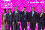 Chinese Premier Li Keqiang, center, waves after posing for a group photo with ASEAN leaders, from left, Myanmar State Counsellor Aung San Suu Kyi, Philippines President Rodrigo Duterte, Singapore Prime Minister Lee Hsien Loong, Thailand Prime Minister Prayuth Chan-ocha, and Vietnam Prime Minister Nguyen Xuan Phuc during ASEAN-China summit in Nonthaburi, Thailand, Sunday, Nov. 3, 2019. (AP Photo/Gemunu Amarasinghe)