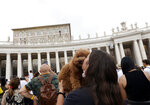 """A girl kisses her dog as Pope Francis, background top, celebrates the Angelus prayer from his studio window overlooking St. Peter's Square at the Vatican, Sunday, July 25, 2021. Pope Francis has offered his blessing for the Tokyo Olympic Games from Vatican City. Francis told the faithful gathered in St. Peter's Square for the traditional papal blessing that """"in this period of pandemic, these Games are a sign of hope, a sign of universal brotherhood and of a healthy competitive spirit."""" (AP Photo/Riccardo De Luca)"""