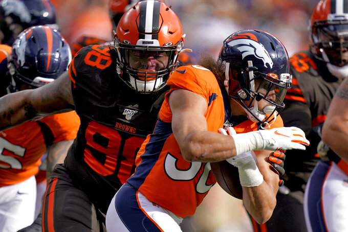Denver Broncos running back Phillip Lindsay, right, tries to avoid Cleveland Browns defensive tackle Sheldon Richardson (98) during the first half of NFL football game, Sunday, Nov. 3, 2019, in Denver. (AP Photo/Jack Dempsey)
