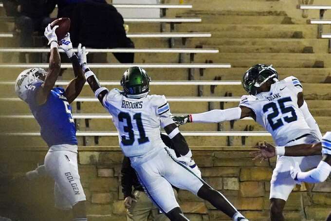 Tulsa wide receiver JuanCarlos Santana (5) catches a pass for a touchdown in front of Tulane safety Larry Brooks (31) and defensive back Kevaris Hall (25) during the second half of an NCAA college football game in Tulsa, Okla., Thursday, Nov. 19, 2020. (AP Photo/Sue Ogrocki)