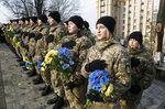 Ukrainian soldiers hold flowers and sing the national anthem at the memorial dedicated to people who died in clashes with security forces at the Independent Square (Maidan) in Kyiv, Ukraine, Tuesday, Feb. 18, 2020. People gathered to commemorate the Maidan protest movement and the events which took place in late Feb. 2014 that led to the departure of former Ukrainian President Victor Yanukovich and the formation of a new government. (AP Photo/Efrem Lukatsky)