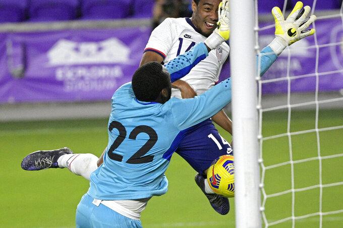Trinidad and Tobago goalkeeper Adrian Foncette (22) blocks a header by United States forward Jonathan Lewis (14) during the first half of an international friendly soccer match, Sunday, Jan. 31, 2021, in Orlando, Fla. (AP Photo/Phelan M. Ebenhack)