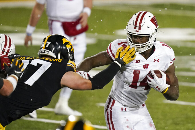 Wisconsin running back Nakia Watson (14) runs from Iowa defensive lineman Zach VanValkenburg, left, during the second half of an NCAA college football game, Saturday, Dec. 12, 2020, in Iowa City, Iowa. Iowa won 28-7. (AP Photo/Charlie Neibergall)