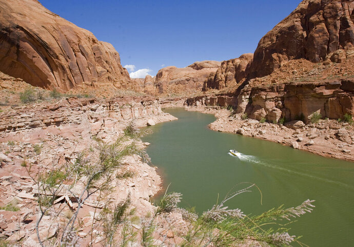 This April 30, 2011 photo shows Lake Powellin southeastern Utah.  A Utah Legislative audit has determined Washington County is expected to pay hundreds of millions of dollars to build and operate a proposed water pipeline.  The state concluded the audit Tuesday, Aug. 20, 2019,  saying the proposed Lake Powell pipeline would require a large fee, rate and tax increases and cost about $1.4 billion over the next 50 years.  Officials say the 140-mile (225-kilometer) line would divert water from the Colorado River across southern Utah each year to the Sand Hallow Reservoir to supply the St. George metro area.   (Al Hartmann/The Salt Lake Tribune via AP)