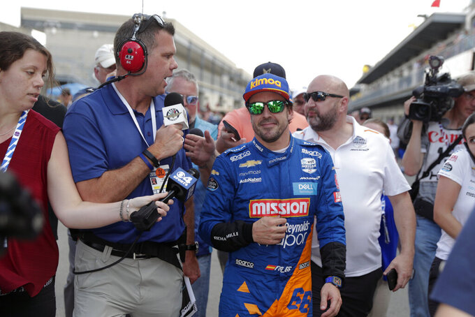 FILE - In this May 18, 2019, file photo, Fernando Alonso, of Spain, is interviewed as he walked from the pit area after qualifications ended for the Indianapolis 500 IndyCar auto race at Indianapolis Motor Speedway in Indianapolis. Alonso feels far better about his chances to close out motorsports' version of the Triple Crown this year. The Spaniard will race for Arrow McLaren SP in the Indianapolis 500 and believes the organization is prepared. (AP Photo/Michael Conroy, File)