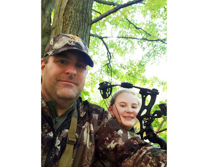 In this Oct. 10, 2020, photo provided by Zane Goucher is Goucher, left, and his daughter Annabelle Goucher bow hunting for deer near Dansville, Mich. Zane Goucher says he hadn't gone hunting in 22 years but took up the sport again because the coronavirus outbreak provided incentive to spend more time outdoors with his children. (Zane Goucher via the AP)