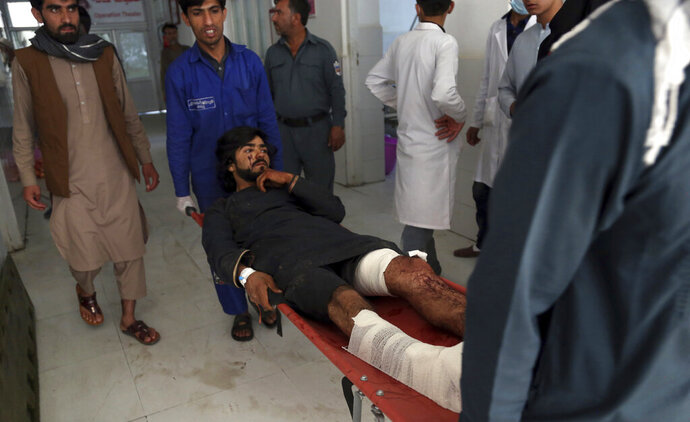 Afghans carry a wounded man into a hospital after a suicide attack in northern Parwan province, Afghanistan, Tuesday, Sept. 17, 2019. The Taliban suicide bomber on a motorcycle targeted presidential guards who were protecting President Ashraf Ghani at a campaign rally in northern Afghanistan on Tuesday, killing over 20 people and wounding over 30. Ghani was present at the venue but was unharmed, according to his campaign chief. (AP Photo/Rahmat Gul)