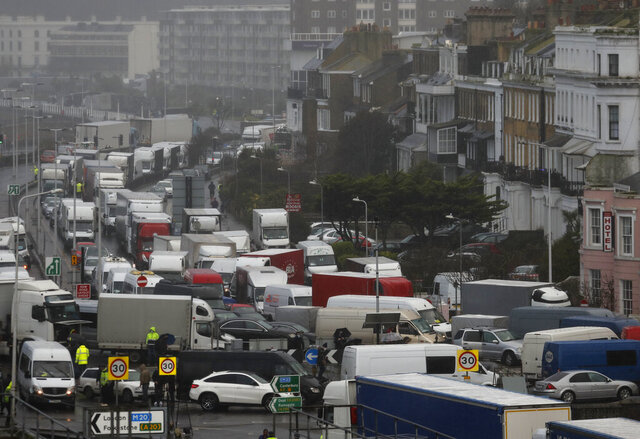 Vehicles wait at the entrance to the Port of Dover, that is blocked by police, as they queue to be allowed to leave, in Dover, England, Wednesday, Dec. 23, 2020. Freight from Britain and passengers with a negative coronavirus test have begun arriving on French shores, after France relaxed a two-day blockade over a new virus variant. The blockade had isolated Britain, stranded thousands of drivers and raised fears of shortages (AP Photo/Frank Augstein)
