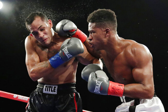 FILE - In this Oct. 27, 2018, file photo, Patrick Day, right, punches Elvin Ayala during the fifth round of a WBC super welterweight boxing bout in New York. Day won the fight. Day died Wednesday, Oct. 16, 2019, four days after sustaining head injuries in a fight with Charles Conwell. Promoter Lou DiBella said Day died at Northwestern Memorial Hospital. He was 27. (AP Photo/Frank Franklin II, File)