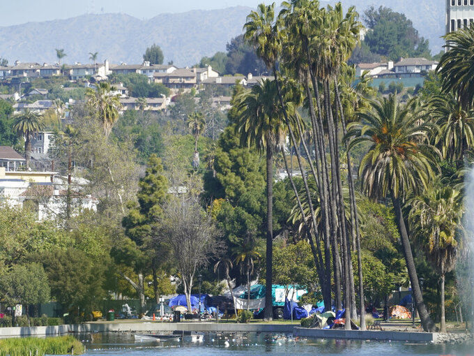 Los Angeles City Sanitation trucks are seen under palm trees around tents set on the north side of Echo Park Lake in Los Angeles Friday, March 26, 2021. A newly installed fence surrounded the park Thursday after a late-night confrontation between police and vocal demonstrators who oppose the city's effort to remove a large homeless encampment and perform extensive repairs of the site. The encampment has been the site of drug overdoses, assaults, and shootings, with four deaths in the park over the past year, according to a statement from City Councilmember Mitch O'Farrell's office.  (AP Photo/Damian Dovarganes)